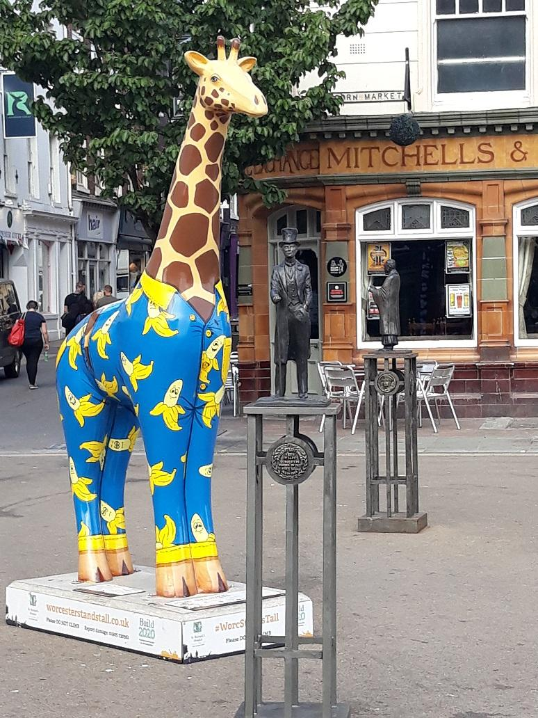 A repaired statue of music hall star Vesta Tilley has returned to Cornmarket next to 'Arthur the Giraffe in Banana Pyjamas' one of the Worcester Stands Tall giraffes.
