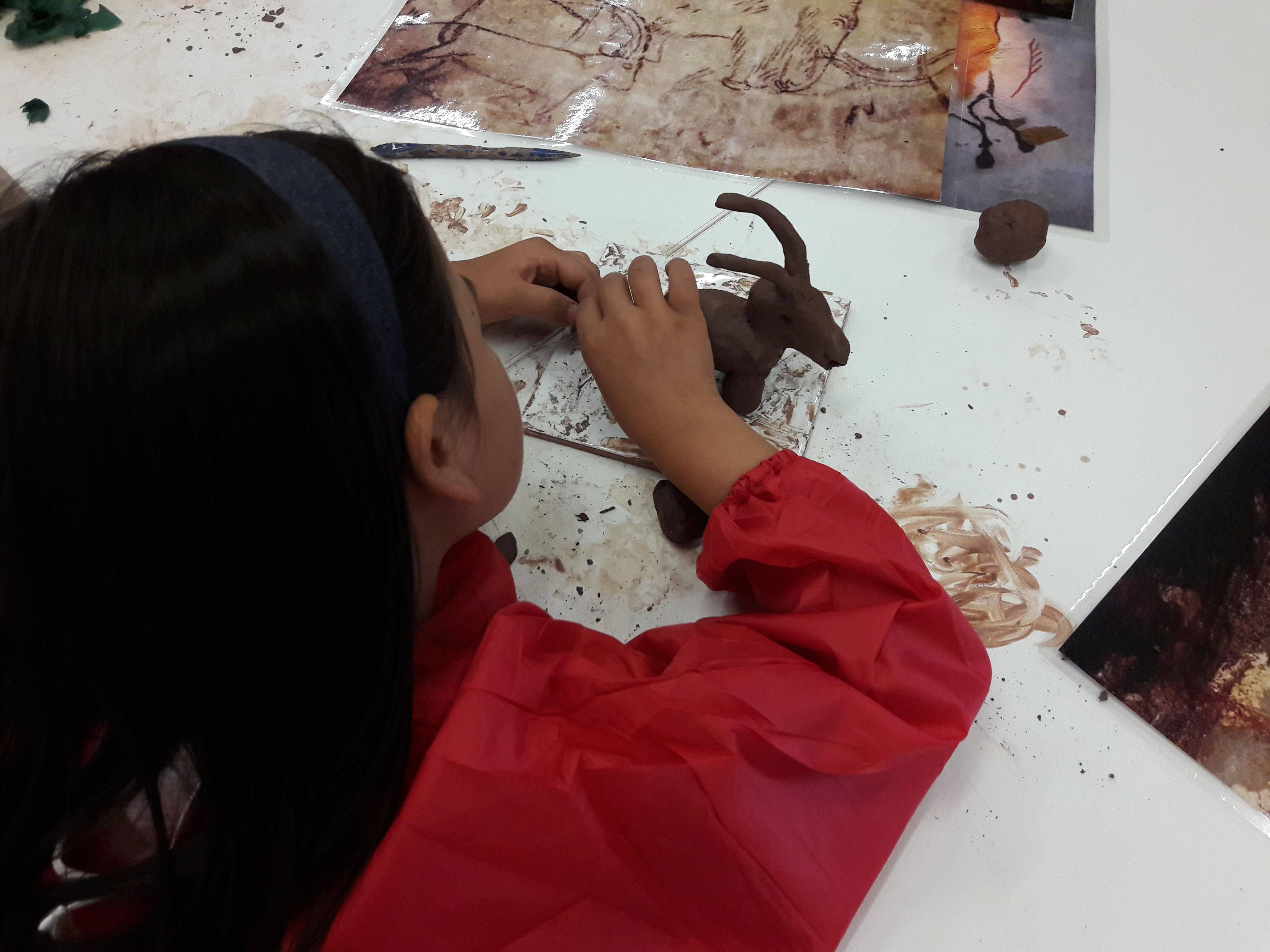 Child making a creature out of clay