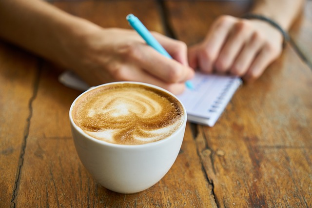 An image of a coffee cup and someone writing a list