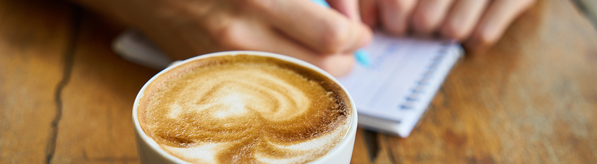 An image of a cup of coffee and someone writing notes on a pad