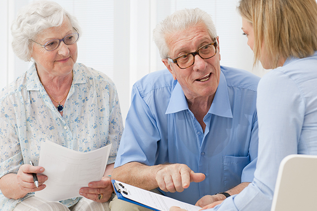 An image of an elderly couple talking to a lady who is taking notes