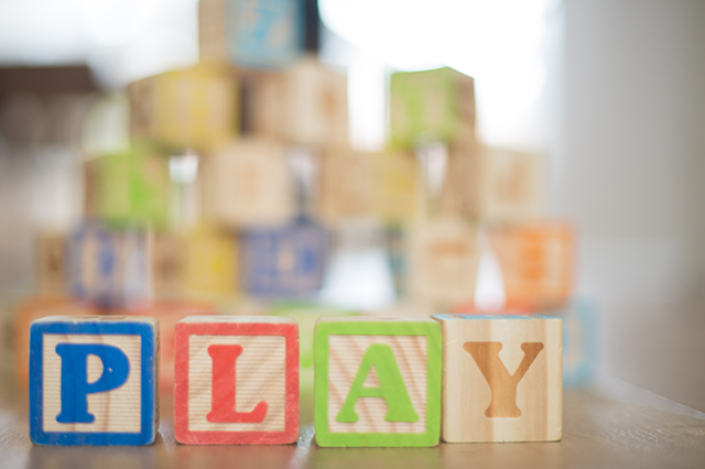 An image of building blocks spelling out the word play