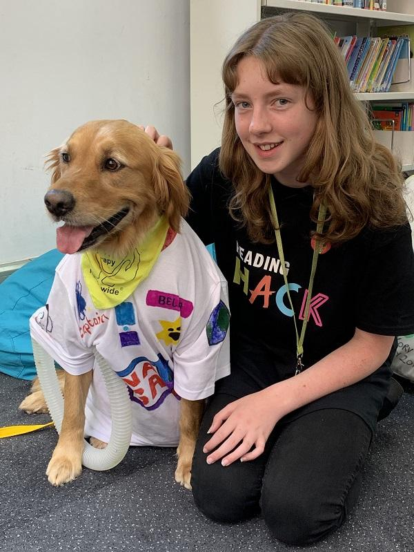 Bella, a trained therapy dog, is posing with a Summer Reading Challenge, volunteer.