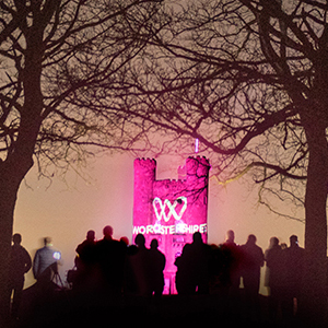 Broadway Tower illuminated pink with the One Worcestershire logo