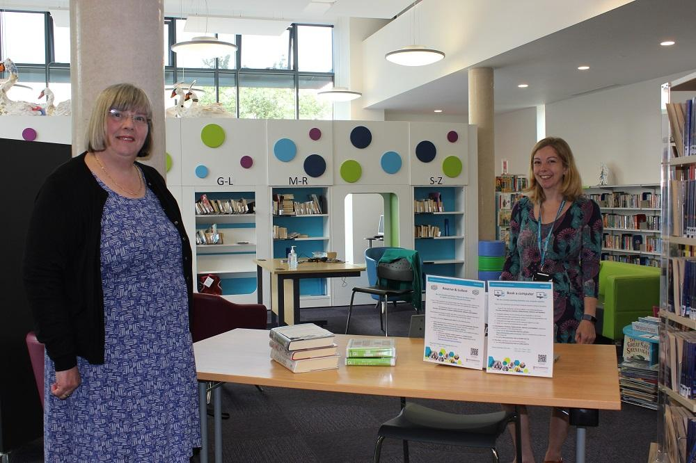 Councillor Lucy Hodgson and Nicki Hitchcock stand near books in Bromsgrove Library.