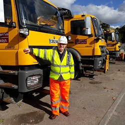 Councillor Alan Amos stood in front of the gritters that are officially on standby.