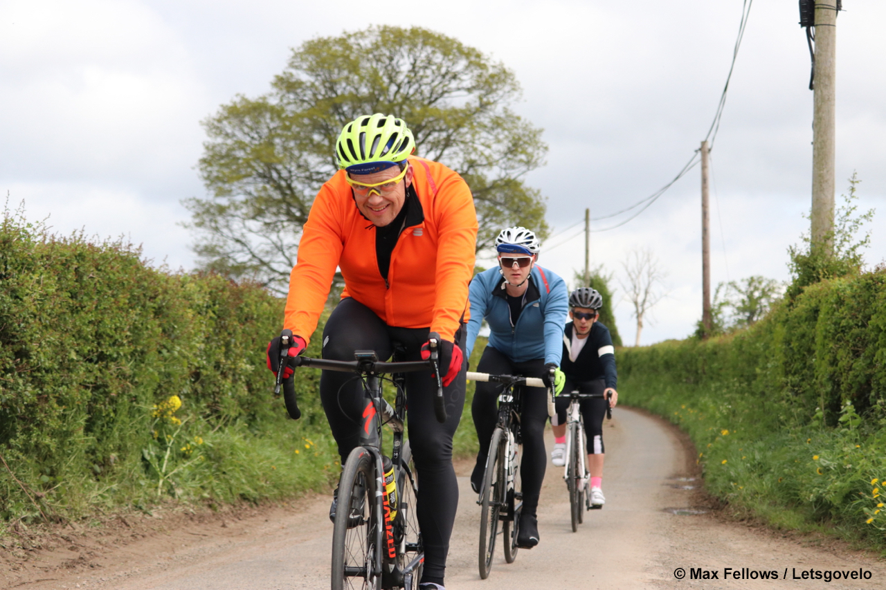 Three cyclists ride down a country lane