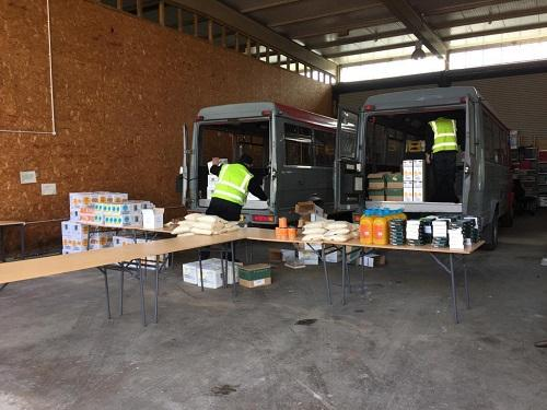 Men are loading food parcels into a van at the depot.