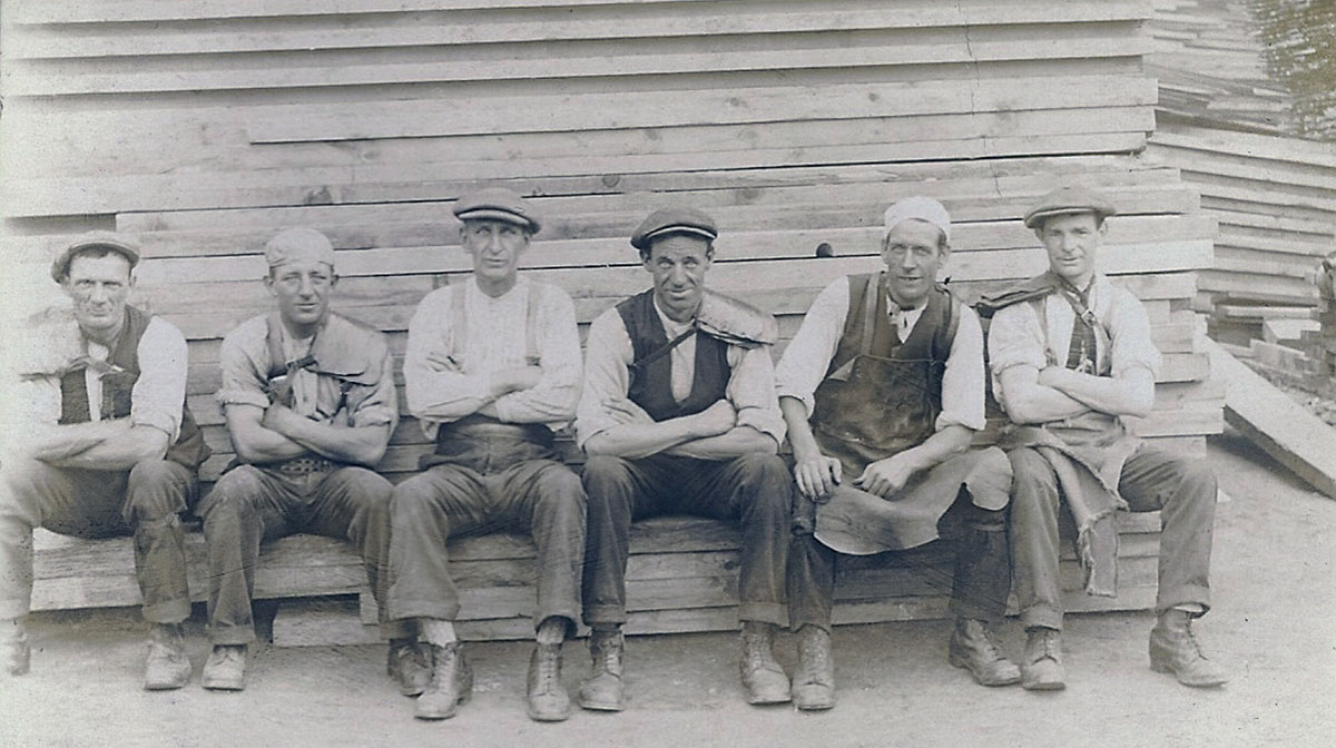 An archive photo showing a group of men sitting on a bench