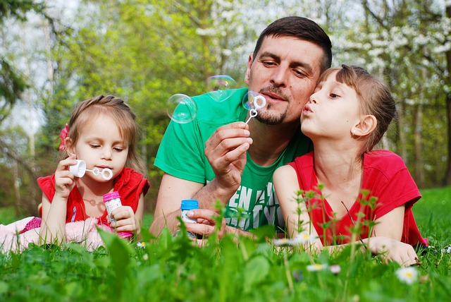 Family support an image of a father and daughters blowing bubbles
