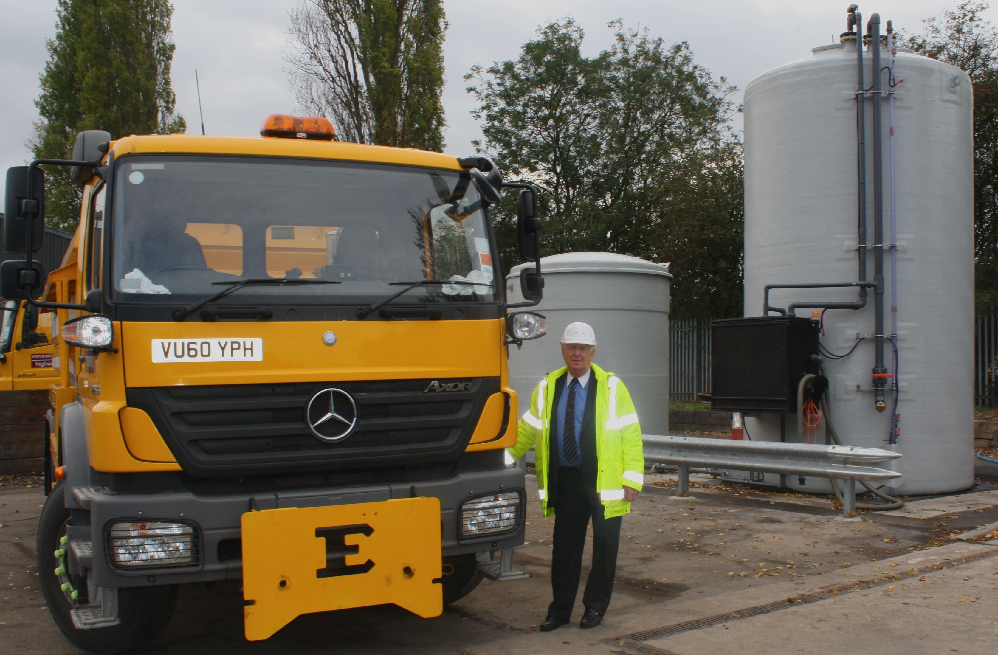 Cllr John Smith OBE, County Council Cabinet Member for Highways, next to a gritter and one of the brine tanks, which stores the solution used to employ the 'pre-wet' technology