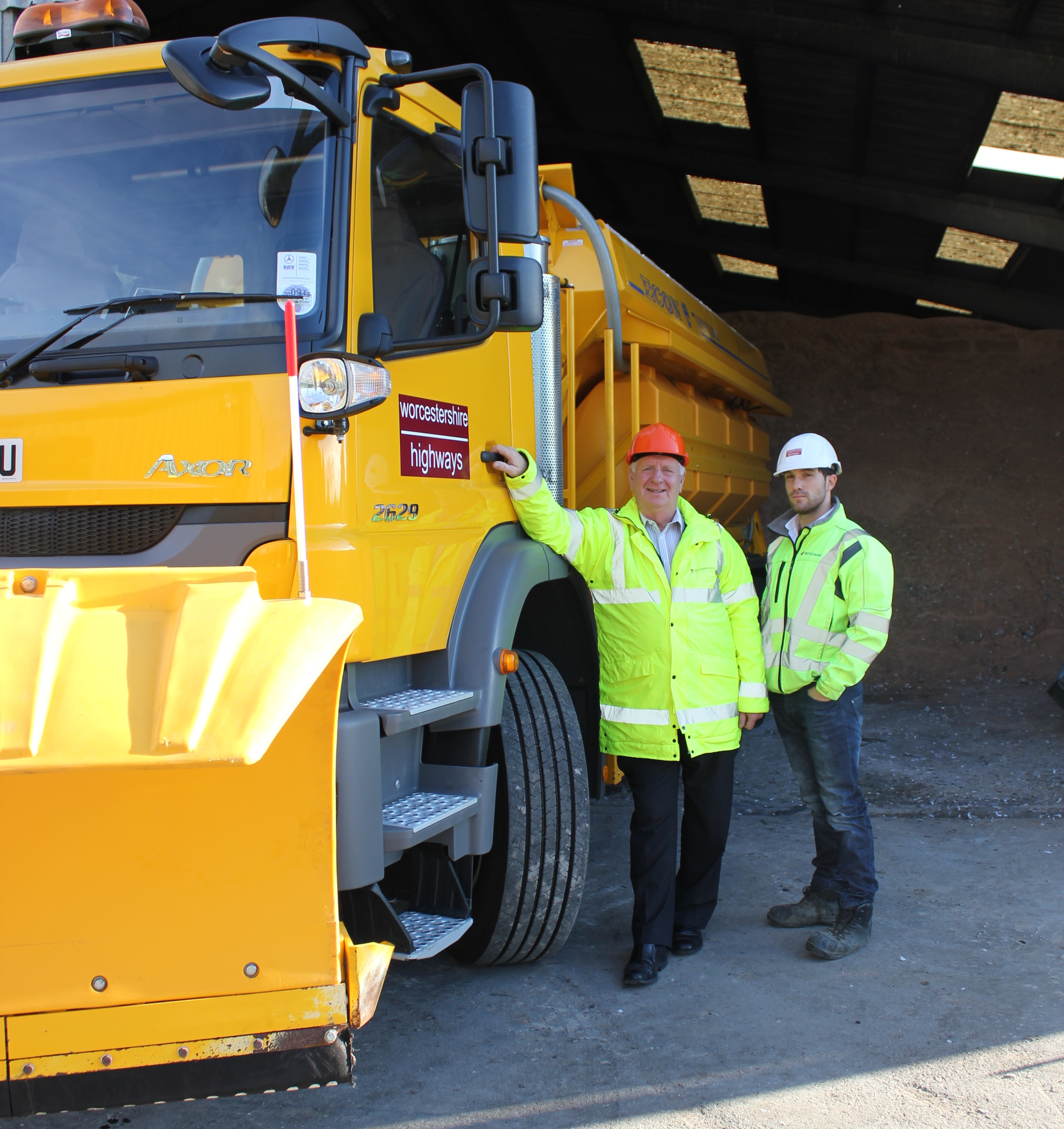 Cllr John Smith OBE, County Council Cabinet Member for Highways, next to a gritter and one of the brine tanks which stores the solution used to employ the 'pre-wet' technology.