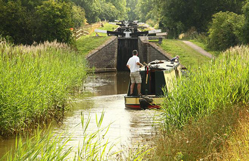 a canal boat drifts down the canal coming to a lock