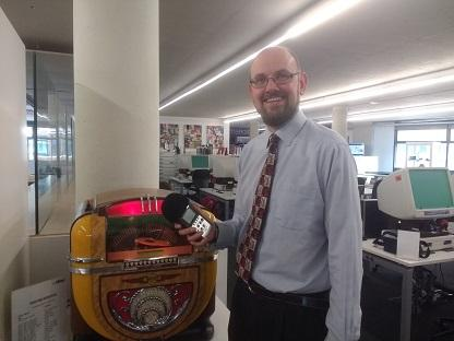 Paul Hudson stands next to a jukebox of audio clips of World War 2