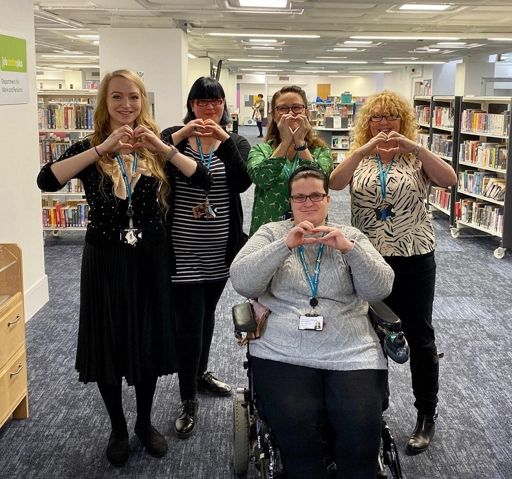 The team at Redditch Library shaping hearts with their hands.