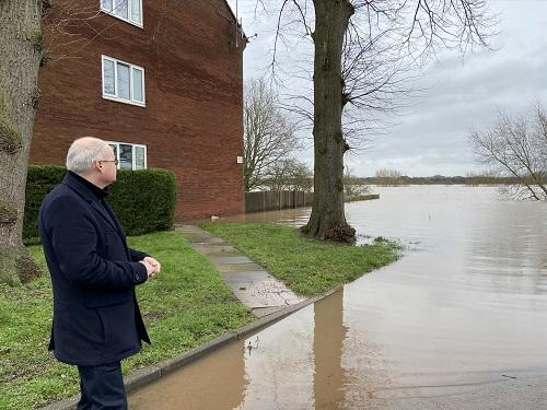 Simon Geraghty stands near floodwater in Upton