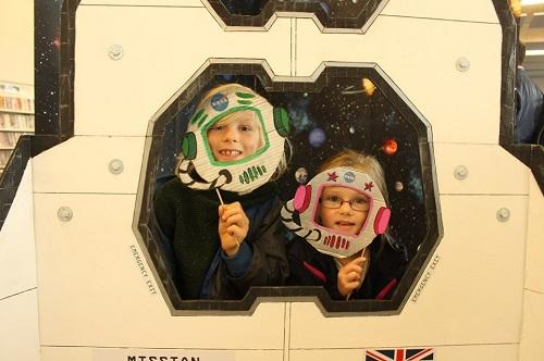 Two children place their faces in a cutout image at a previous Space Day.