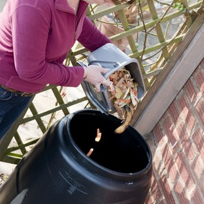 woman pouring into a compost bin