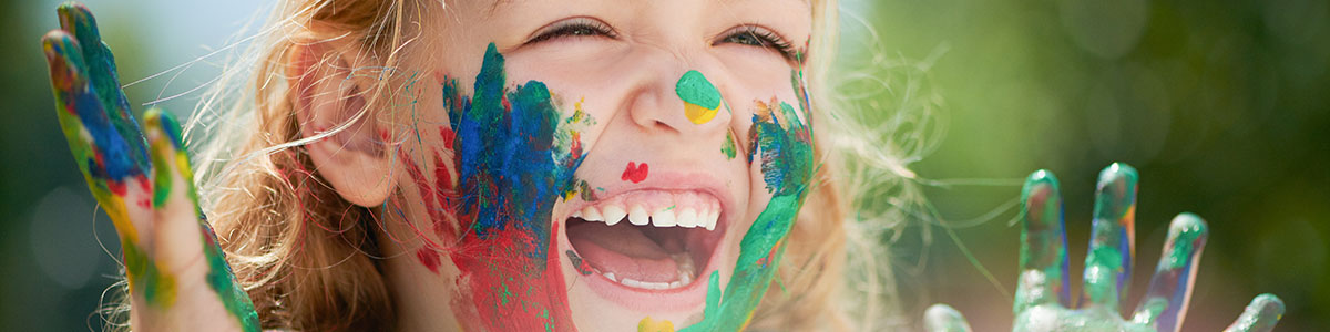 An image of a girl with paint on her hands and face